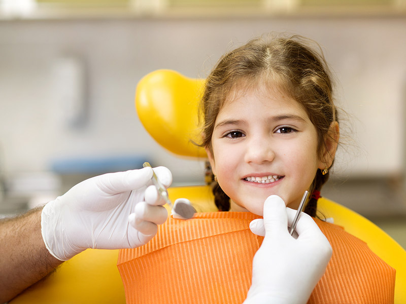 Little girl sitting and smiling on dentist chair