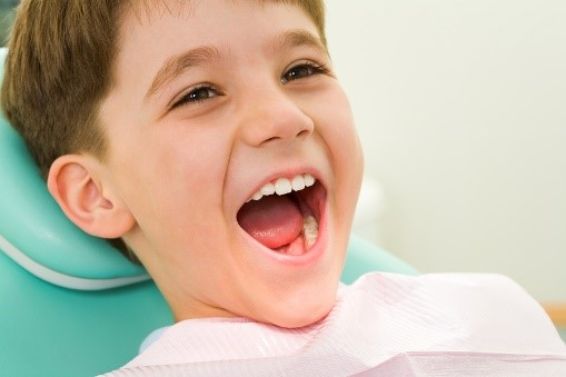 Boy sitting in dentist chair with mouth wide open
