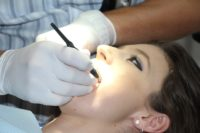 female patient being checked by a dentist