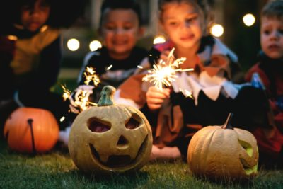 children with sparklies and jack o' lanterns on Halloween