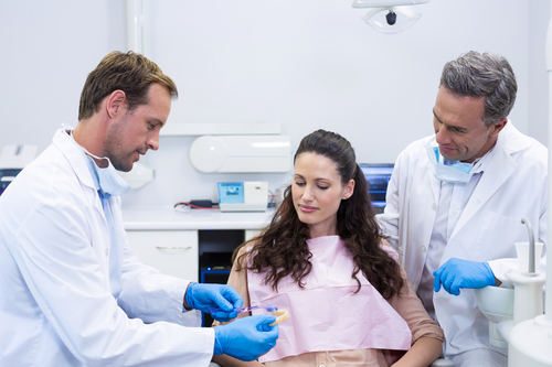 dentist showing model teeth to a female patient