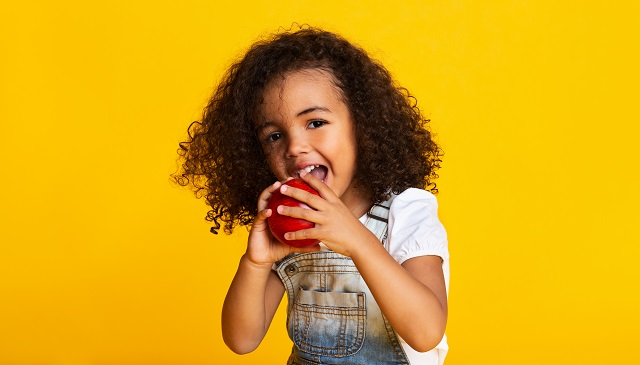 little girl biting red apple