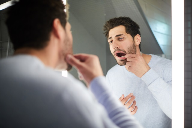 young man checking tooth in bathroom mirror