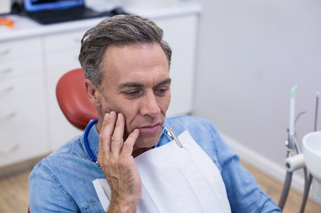 unhappy man with toothache touching his cheek