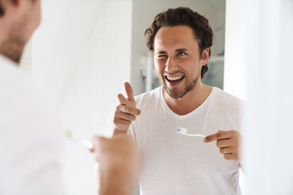 man pointing at a mirror while holding a toothbrush