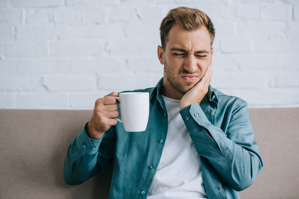 man suffering from tooth pain while holding a white cup